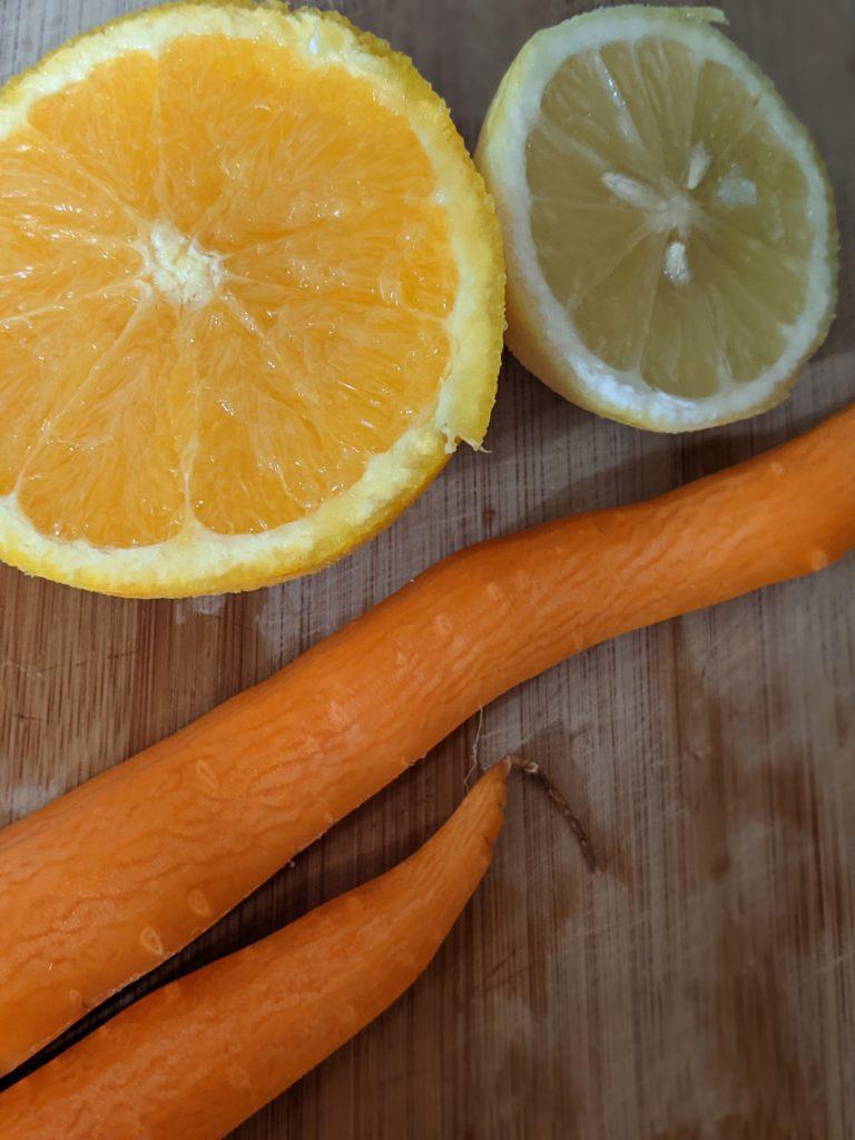 A sliced orange, a sliced lemon, and peeled carrots rest on a cutting board.